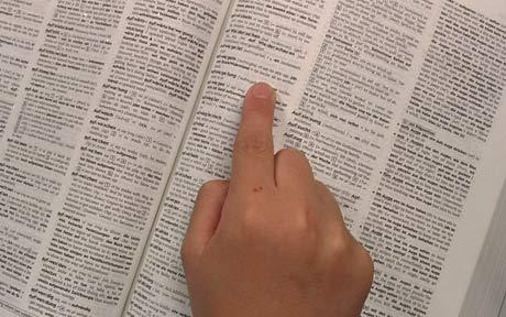Image of a finger pointing at an entry in a dictionary.